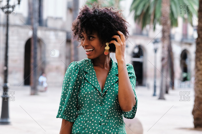 Happy young African American female with curly hair and stylish earrings wearing trendy green polka dot blouse looking away while standing against blurred urban background