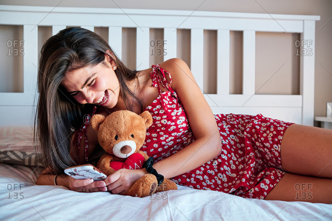 Positive young female in casual dress lying on bed with teddy bear and browsing internet on mobile phone while enjoying free time at home