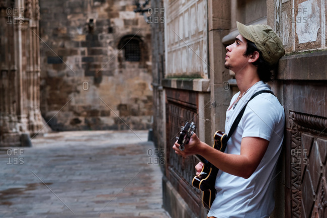 Side view of young male guitarist playing musical instrument on old city street and looking up