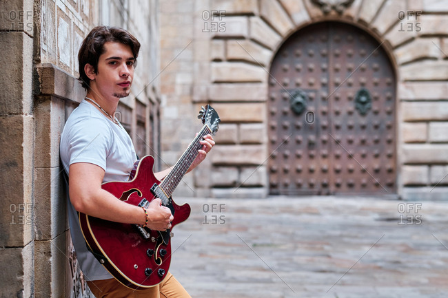 Side view of young male guitarist playing musical instrument on old city street and looking at camera