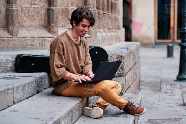 Positive male entrepreneur sitting on stone steps in city and working on remote project while browsing netbook