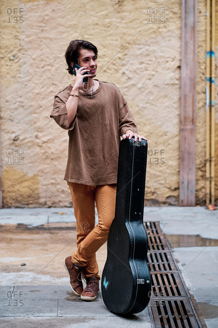 Male musician with guitar in case standing on shabby street and discussing songs on smartphone while looking away