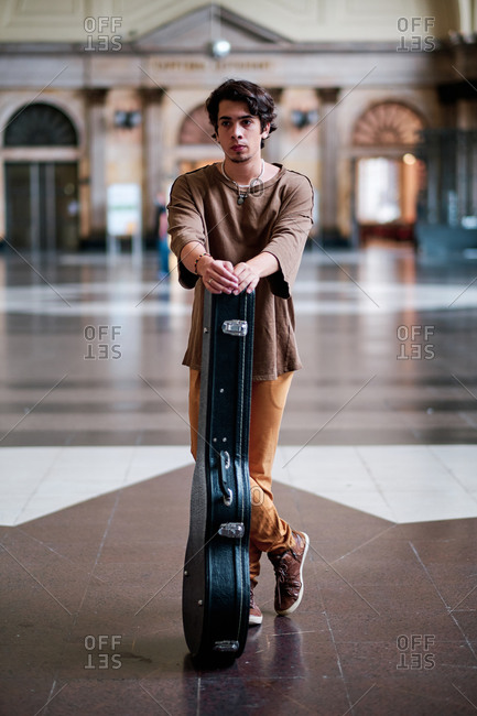 Pensive male musician with guitar in solid case standing in spacious hall of city building and looking away