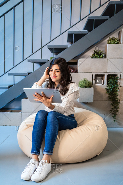 Full length of focused young female designer in casual clothes sitting on comfortable pouf and using graphic tablet while working in contemporary creative workspace