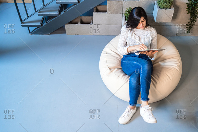 Top view full length of focused young female designer in casual clothes sitting on comfortable pouf and using graphic tablet while working in contemporary creative workspace