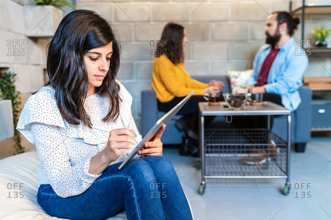 Serious young female designer in casual outfit working on project with modern graphic tablet while sitting in creative workspace with colleagues in background