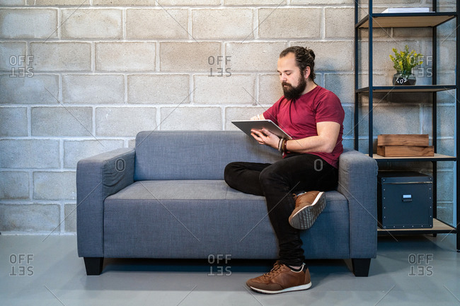 Full body of focused young bearded male freelancer in casual outfit sitting on sofa and using tablet while working on project in contemporary loft workspace