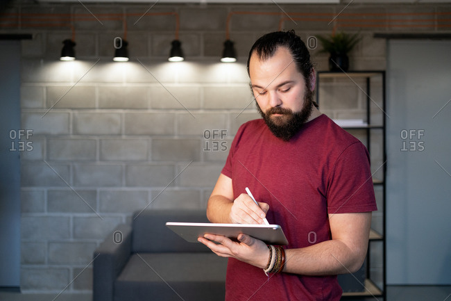 Focused young bearded male freelancer in casual outfit standing using tablet while working on project in contemporary loft workspace