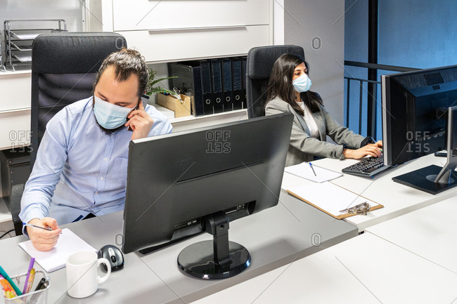 Serious focused young man in medical mask discussing business issue by phone while female colleague working with computer in contemporary coworking office