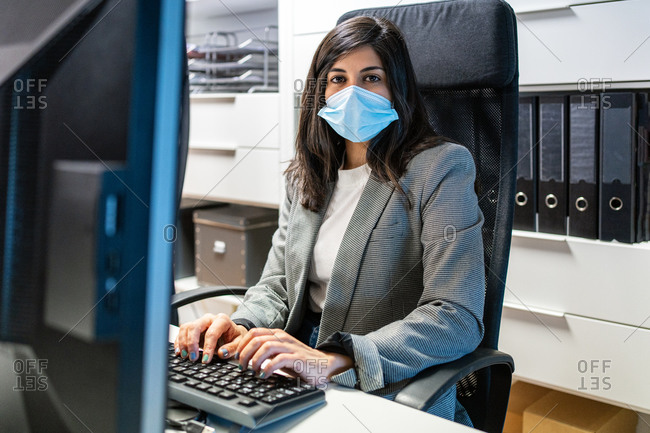Confident young female specialist in formal suit and protective mask sitting at desk and using computer while working in modern workspace looking at camera