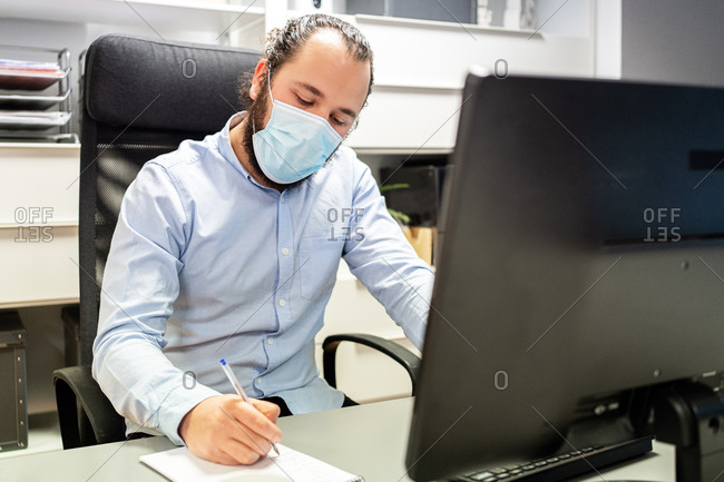 Focused young bearded male manager in formal blue shirt and protective mask making notes in notebook while sitting in chair in front of computer monitor in modern workplace
