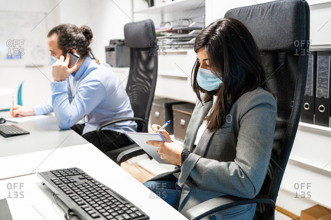 Serious young female employee in formal clothes and protective mask sitting at desk with computer and writing in notebook while working in contemporary workspace with colleague