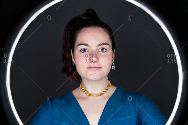 Charming female illuminating face with circle lamp while standing in dark studio and looking at camera