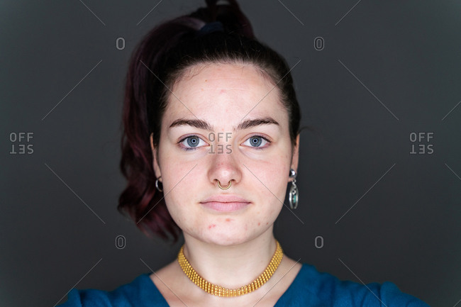 Calm female with problematic skin and without makeup standing in studio on black background and looking at camera