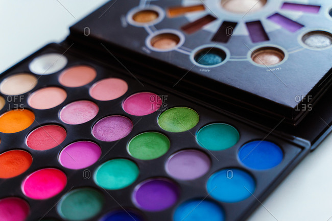 Closeup of multicolored palette with various eyeshadows placed on table in modern  beauty salon