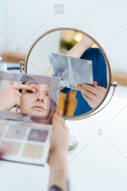 Concentrated female sitting at table with assorted cosmetics and applying eyeshadow on eyelid with finger while looking in round mirror