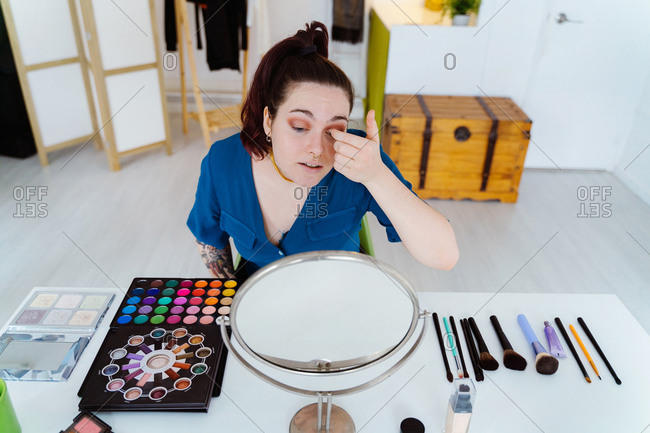 High angle of concentrated female sitting at table with assorted cosmetics and applying eyeshadow on eyelid while looking in round mirror