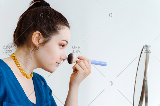 Side view of female makeup artist smearing foundation cream on face looking at round mirror
