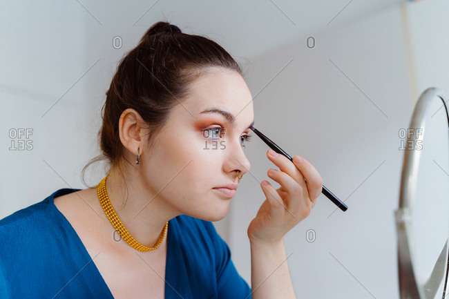 Side view of young beautiful female makeup artist sitting at table with eyeshadow palette applying makeup with brush