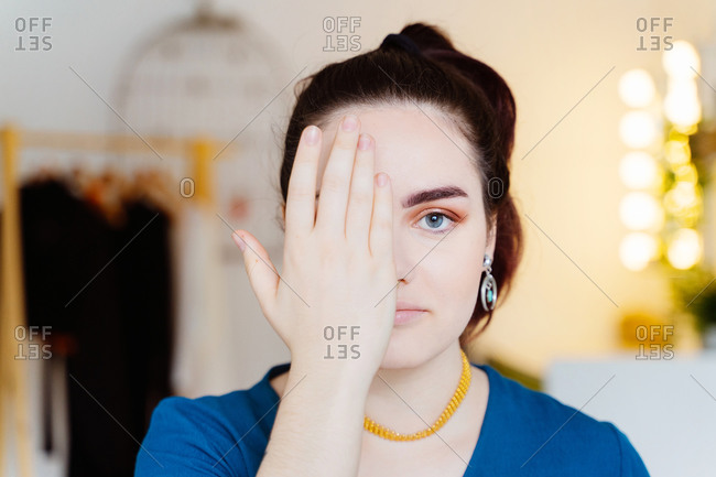 Young female with professional makeup and piercing standing in modern beauty salon while covering eye and looking at camera