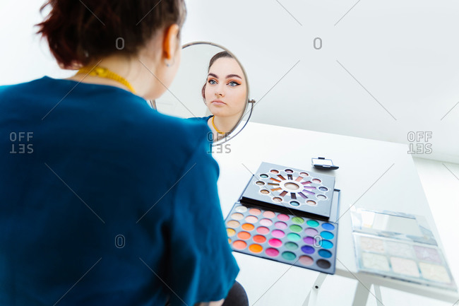 Young beautiful female makeup artist sitting at table with eyeshadow palette applying makeup with brush