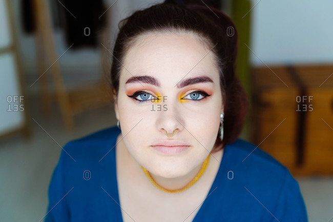Content female makeup artist sitting at table looking at camera