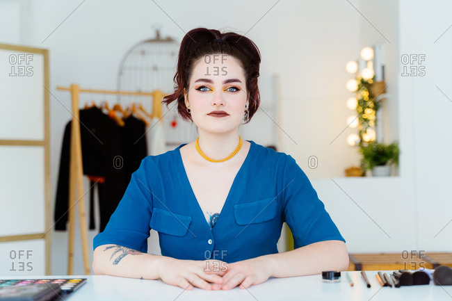 Content female makeup artist sitting at table with assorted cosmetic products and tool while looking at camera