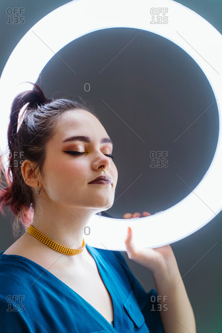 Side view of female with professional makeup and in stylish wear standing in studio holding circle lamp on grey background with eyes closed