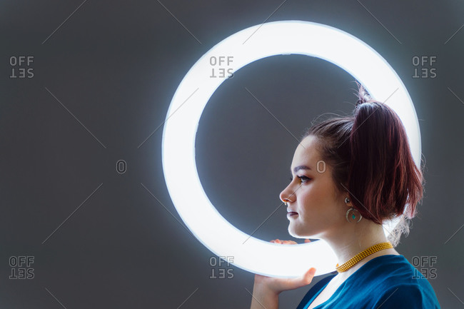 Side view of female with professional makeup and in stylish wear standing in studio holding circle lamp on grey background and looking away