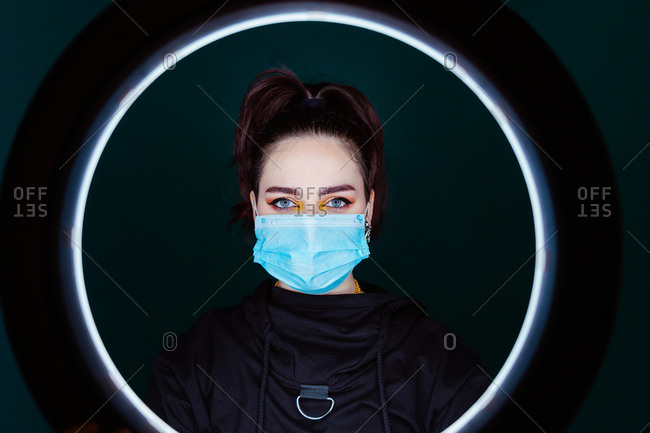 Calm female wearing medical mask standing in modern studio and looking at camera through ring lamp on black background
