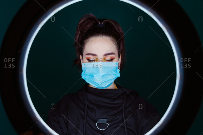 Calm female wearing medical mask standing in modern studio with eyes closed through ring lamp on black background