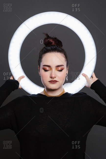 Female with professional makeup and in stylish wear standing in studio holding circle lamp on grey background with eyes closed