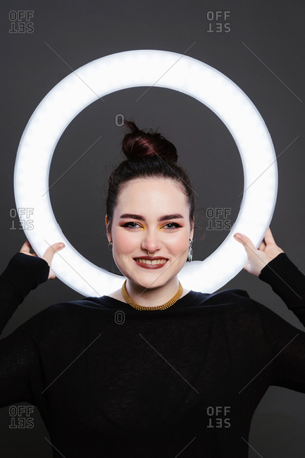 Delighted female with professional makeup and in stylish wear standing in studio holding circle lamp on grey background and looking at camera