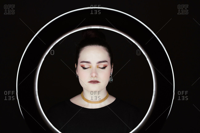 Female with professional makeup and in stylish wear standing in studio behind ring circle lamp on black background with eyes closed