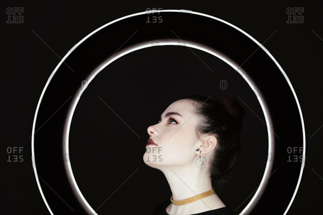 Side view of female with professional makeup and in stylish wear standing in studio behind ring circle lamp on black background and looking away