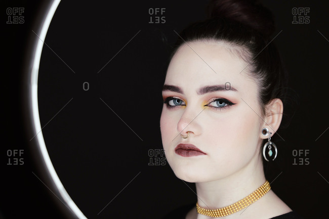 Female with professional makeup and in stylish wear standing in studio behind ring circle lamp on black background and looking at camera