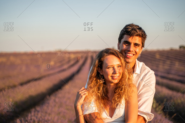 Affectionate young couple hugging while standing in lavender field in summer evening during romantic holidays