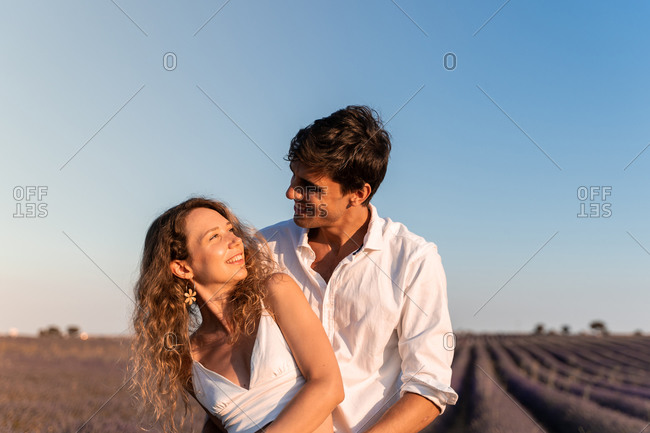 Affectionate young couple hugging while standing in lavender field in summer evening during romantic holidays looking at each other