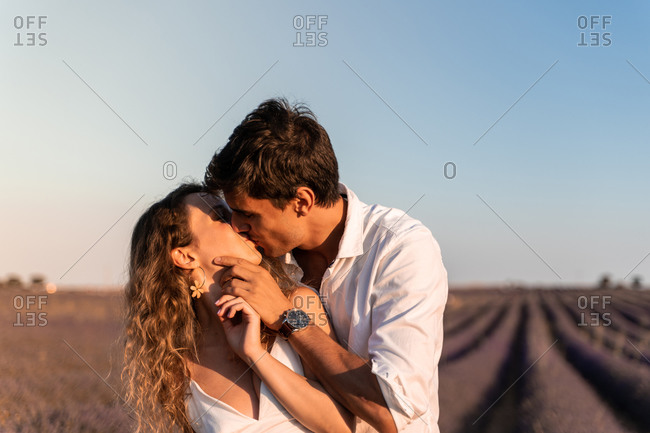 Affectionate young couple hugging and kissing while standing in lavender field in summer evening during romantic holidays
