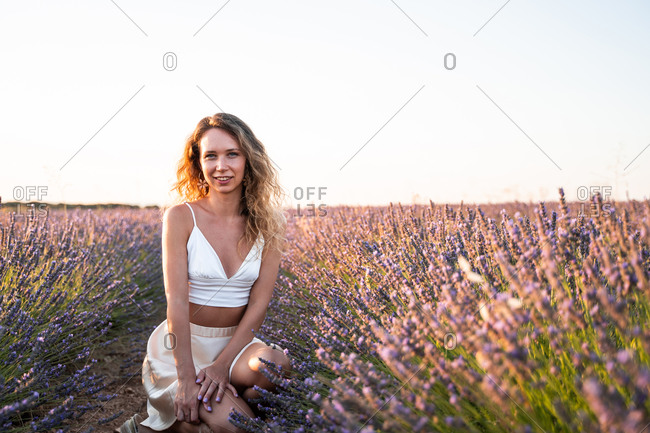 Carefree romantic young female in summer outfit sitting amidst lavender field looking at camera in summer evening