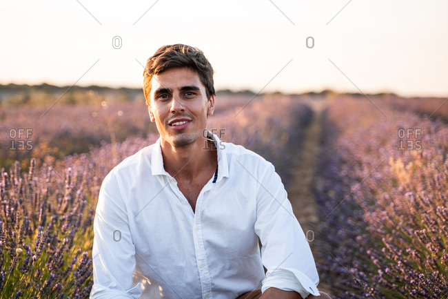 Positive handsome young male in white shirt and shorts smiling and looking at camera while enjoying summer evening amidst lavender flowers in countryside