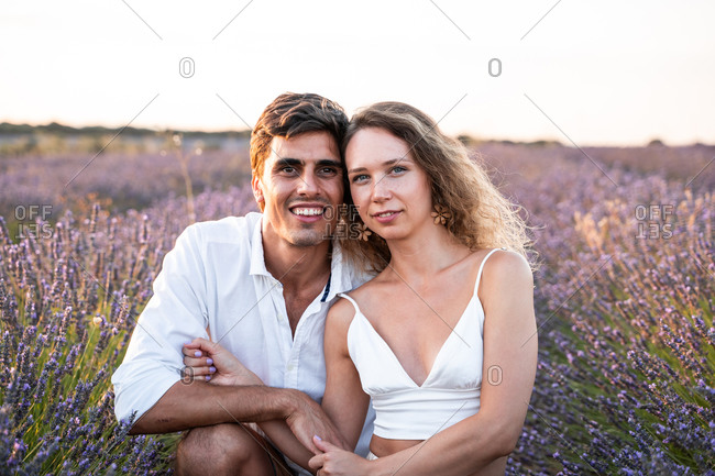 Happy young man and woman sitting together among lavender flowers and enjoying summer evening together during romantic holidays in countryside