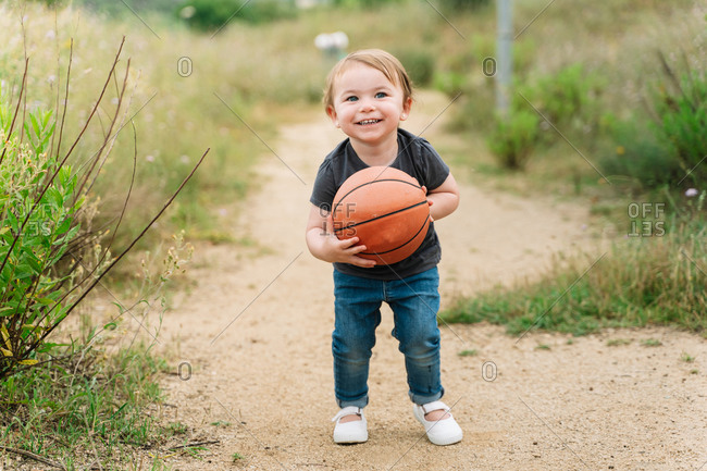 Adorable little child walking with basketball while having fun in rural area during weekend