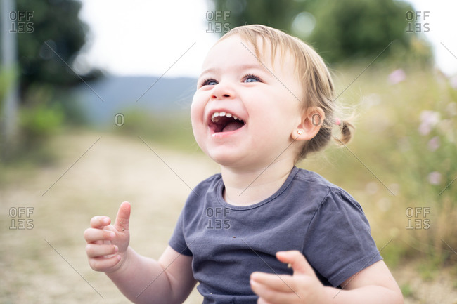 Cheerful little girl with cute ponytails laughing happily while having fun during summer day in nature