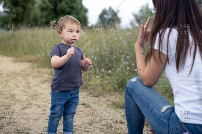 Side view of adorable toddler girl in casual clothes standing on ground and playing with happy mother while spending summer day together in countryside