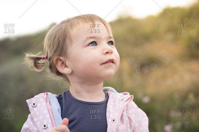 Cheerful little girl with cute ponytails smiling while having fun during summer day in nature