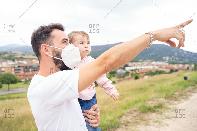 Positive young bearded man in protective mask holding cute toddler daughter while standing against blurred countryside background in summer day