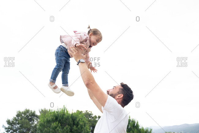 Low angle happy father holding excited toddler child in raised arms while having fun and playing together outdoors in summer day