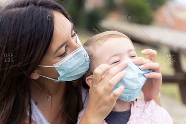 Caress young woman in medical mask adjusting mask on face of toddler child while spending time together outdoors