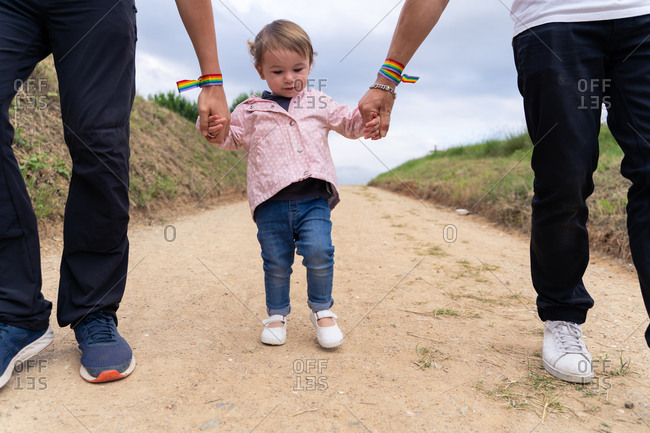 Cute little girl in casual wear holding hands of crop unrecognizable parents with rainbow bracelets while walking together on narrow path in summer countryside